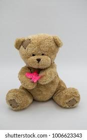 teddy bear holding pink butterfly