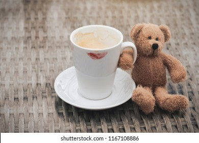 Teddy bear holding white cup of hot coffee with mark lips on the top,Mug coffee latte with red lipstick mark on rattan table with brown bear in retro filter.