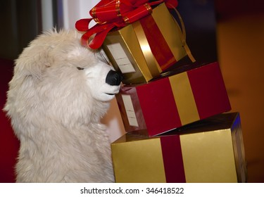teddy bear holding wrapped colorful gifts for Christmas