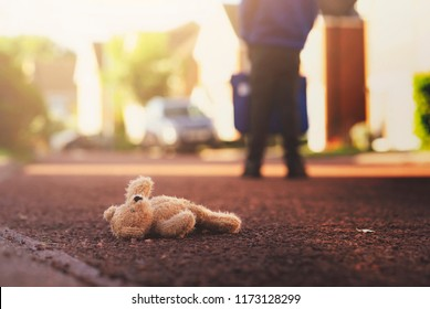 Teddy bear laying on the road with blurry background of school kid carrying school bag,Lonely brown bear was left lying on the street,little boy is growing to big boy he doesn't want cute toy anymore