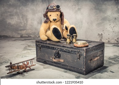 Teddy Bear with leather aviator's hat and goggles sitting on vintage old classic travel trunk circa 1900s with binoculars, compass, wooden toy plane. Travel by air concept. Retro style filtered photo