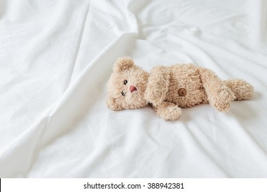 Teddy Bear lying in the bed .