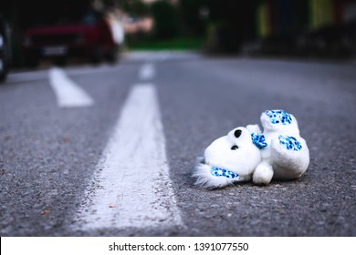 Teddy bear lying in the middle of the road.
