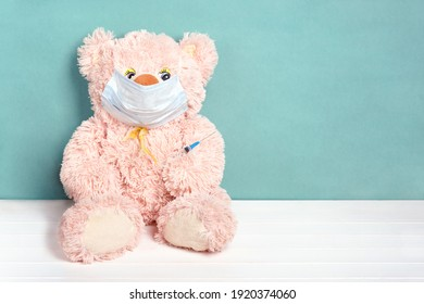 Teddy bear in medical mask with syringe. Coronavirus vaccination. Covid-19 vaccine concept. Copy space.