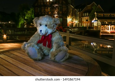 Teddy bear at night on a wooden plate