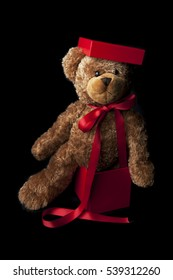 Teddy bear on black background wrapped up as a Christmas gift with red ribbon and a box