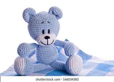 teddy bear on blue and white picnic blanket