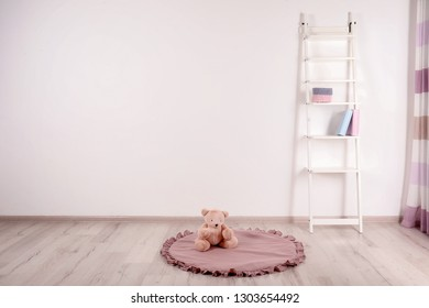 Teddy bear on floor and shelving unit near wall in child room. Space for text