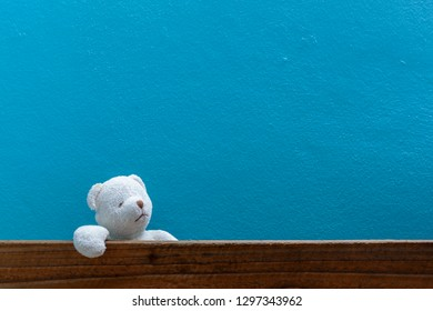 Teddy bear on old wood in front blue wall background.