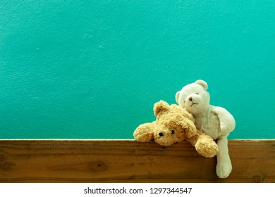 Teddy bear on old wood in front green wall background.