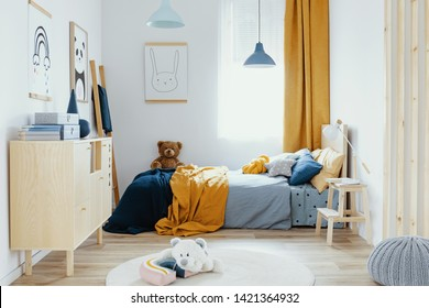 Teddy bear on single wooden bed in blue and orange bedroom interior