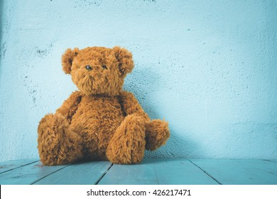 Teddy bear on a table have blue background, alone