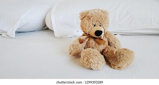 Teddy bear on white bed