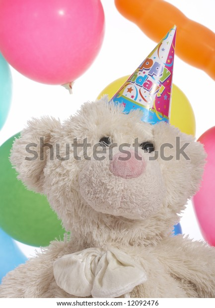 teddy bear with party hat over the balloons