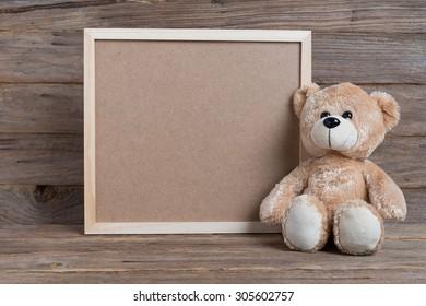 Teddy bear and photo frame on wood