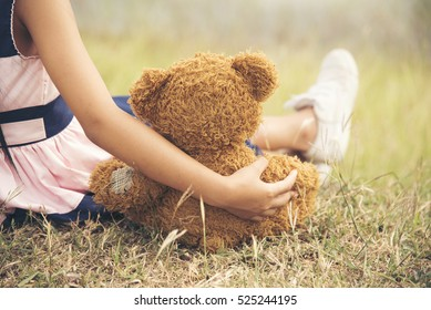 Teddy Bear picnic happy child girl kid holding fluffy toy with little hand sitting on grass field. cute girl love teddy bear best friends hug holding together. Kids on playground Picnic Best Friend