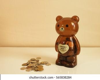 Teddy bear piggy bank with saving coins.