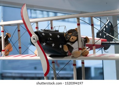 Teddy bear in pilot's glasses and pilot's jacket on the wing of an old airplane. storefront.