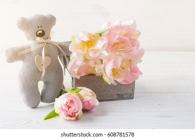 Teddy Bear with pink tulips on white wooden background. Toned image