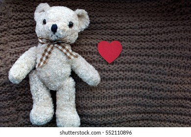 Teddy bear and red heart on knitted background