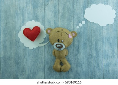 Teddy Bear and red heart in thought bubble on wood background.