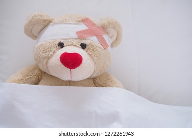 Teddy bear, red nose, lying sick in bed With a headband and a cloth covered