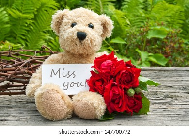 teddy bear with red roses  and card with lettering miss you/miss you/teddy