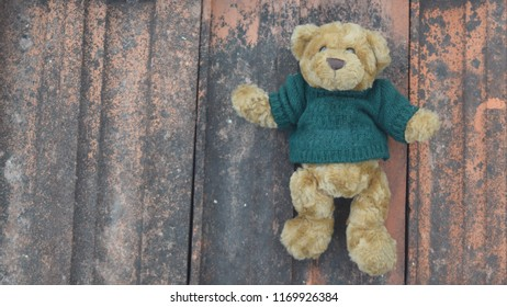 A teddy bear relaxing on roof tiles.