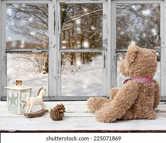 teddy bear and rocking horse looking at snowy day