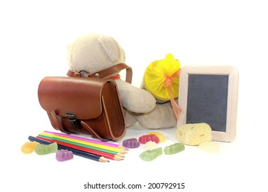 Teddy bear with school bag, wallet, pens and board on a light background