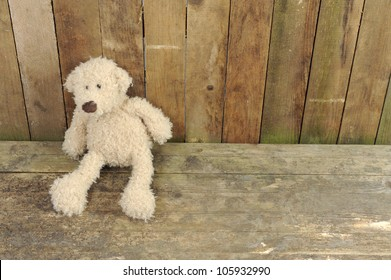 teddy bear seated against a old wooden wall