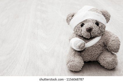 Teddy bear sick with bandages and broken hand on old wood background with copy space, black and white tone.