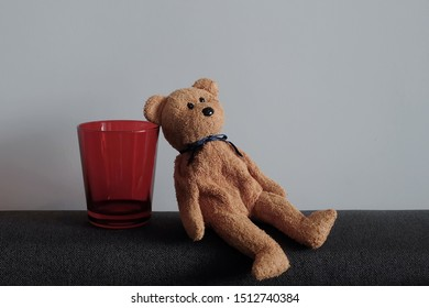 Teddy bear sit on floor with big red glass. Lonely, Sad, alone bear doll with white background. Tired bear. lean to rest. Break, Relax, Nap, Fail, Childhood memory, toy, Imaginary friend, Furry doll