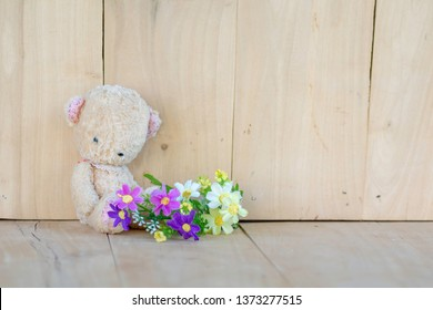 Teddy Bear Sit on a wooden floor and bouquet of flowers.