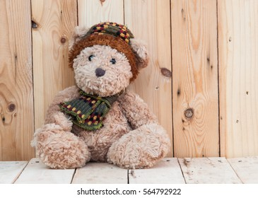 Teddy bear sit on wooden background.
