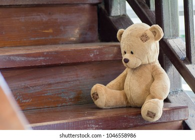Teddy Bear Sit at the wooden stairs.