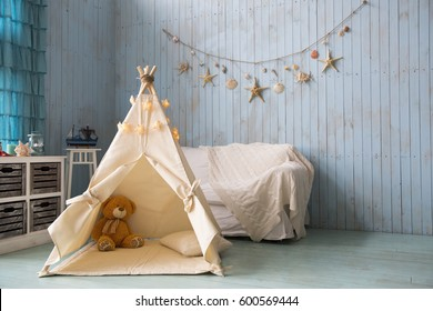 Teddy bear sits in a children's house wigwam on the background of an old wooden blue wall