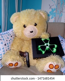 A teddy bear sits on a sofa and holds a nuclear suitcase in one hand and a Makarov pistol in the other.