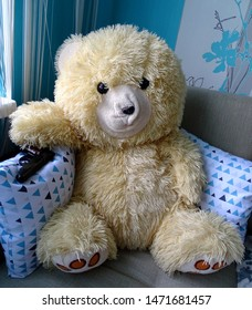 A teddy bear sits on a sofa and holds a Makarov pistol in his hand