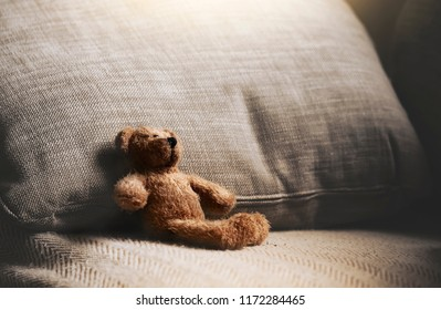 Teddy bear sitting down on sofa in retro filter, Lonely teddy bear sitting alone on couch in living room at night,Lonely concept,Lost child,International missing children's day.