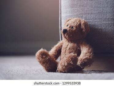 Teddy bear is sitting down on carpet in retro filter, Lonely teddy bear sitting alone in living room in gloomy day, Lonely concept, International missing children's day.