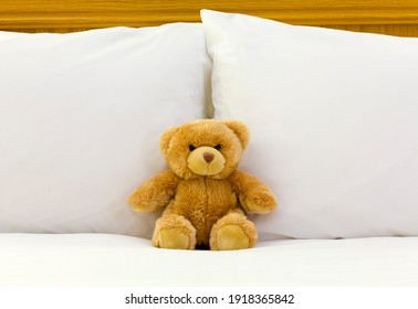 Teddy bear sitting on a bed with crisp white sheets. Hotel or home bedroom interior design UK
