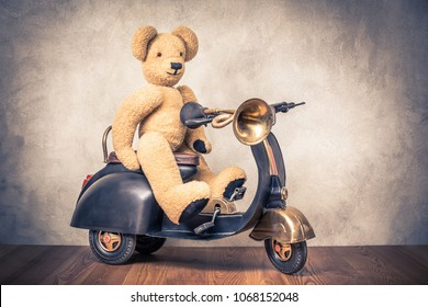 Teddy Bear sitting on old black retro toy pedal scooter trike with classic klaxon in front concrete textured wall background. Vintage style filtered photo