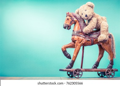 Teddy Bear sitting on vintage antique Christmas wooden horse toy on wheels front mint green wall background. Holiday greeting card concept. Retro instagram style filtered photo
