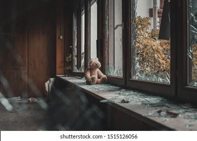 teddy bear sitting on windowsill. Looking through broken window glass