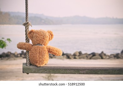 Teddy Bear sitting on the wooden swing with blue sea and sky background. Concept about loneliness and waiting for someone (Vintage Style)