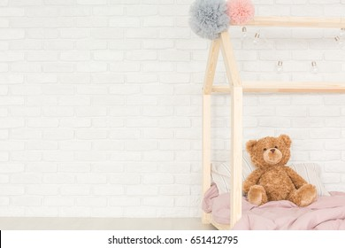 Teddy bear sitting on wooden baby bed against brick wall