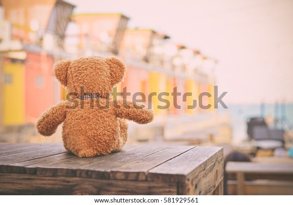 Teddy bear sitting on the wooden box with love. Concept about loneliness or waiting for someone.(Vintage Style)
