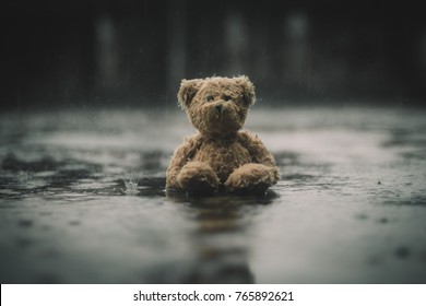 Teddy Bear with sitting in the raining and vintage filter effect blurred background of nature.