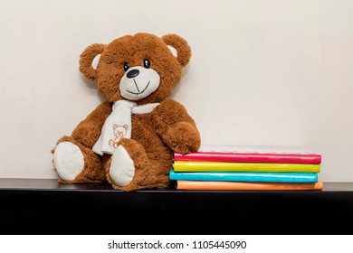Teddy bear soft toy in child's bedroom with colorful books